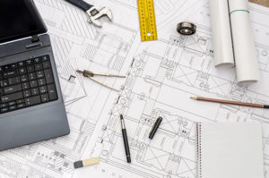 Building plans underneath a laptop and other tools representing the philosophy of general contractor Via Meridiana Contractors LLC in Westmont, IL